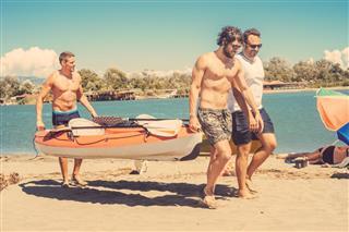 Three friends carrying canoe