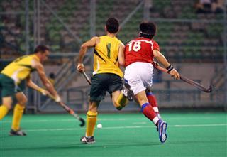 Three players playing hockey