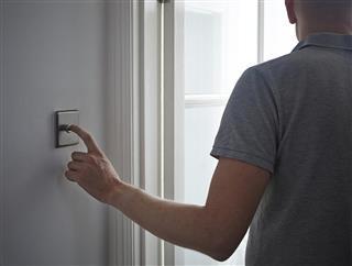 Man turning off light switch