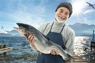Fisher holding a big atlantic salmon fish