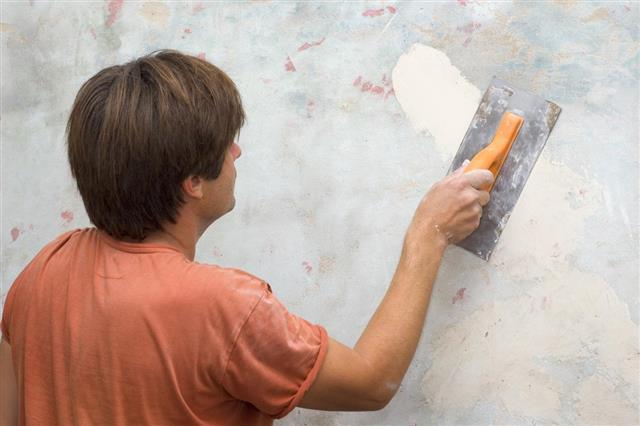 Man Repairing Wall Cracks