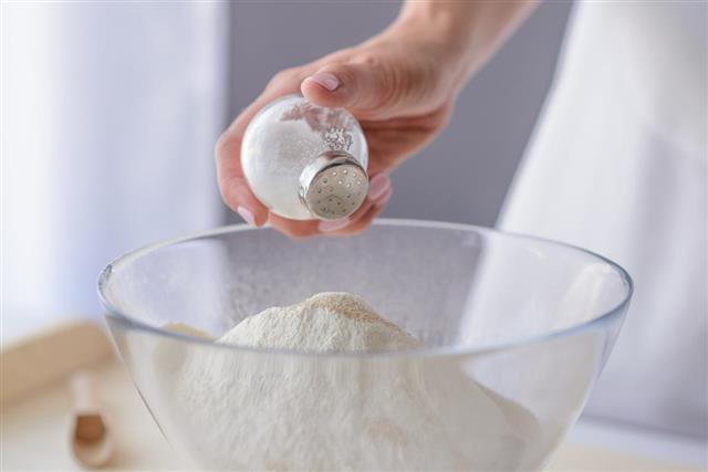 Woman adding salt to flour