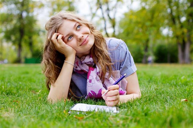 Teenage girl making homework in park