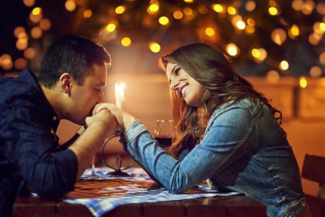 Man kissing woman hand