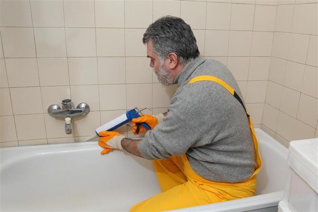 Worker caulking bath tube and tile