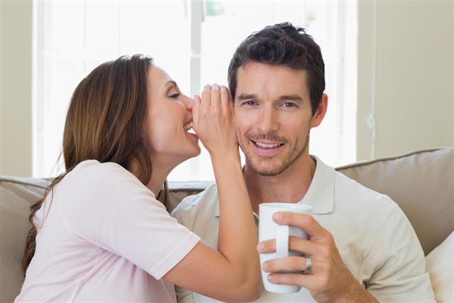 Woman whispering secret into a happy mans ear