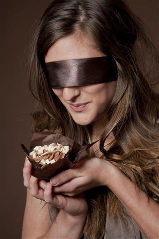 Blindfolded woman holding chocolate cake