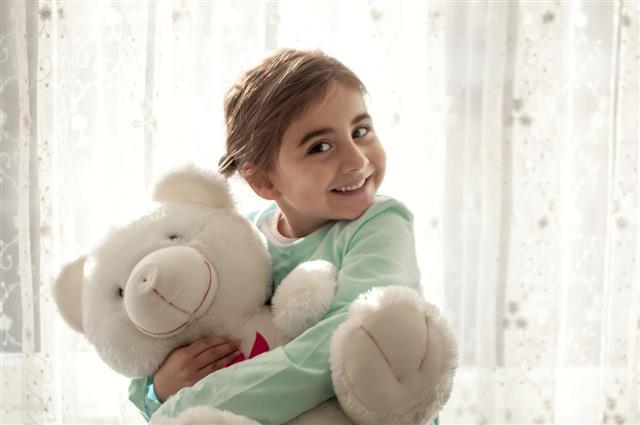 Cute girl hugging her teddy