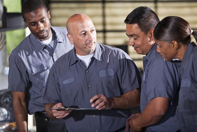 Team of mechanics looking at clipboard