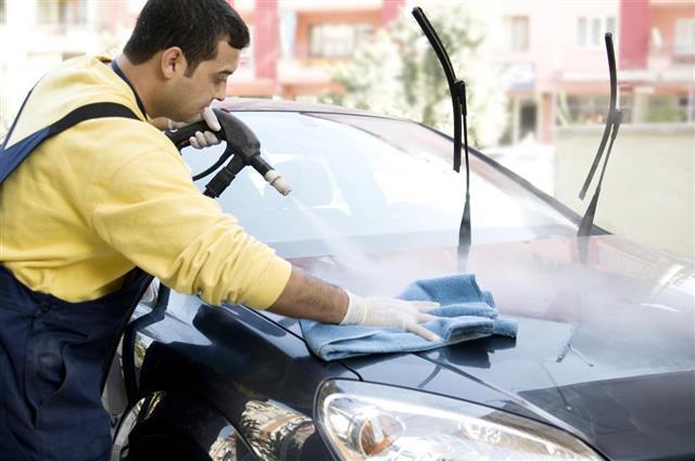 Car wash staff washing cars with high pressure water gun