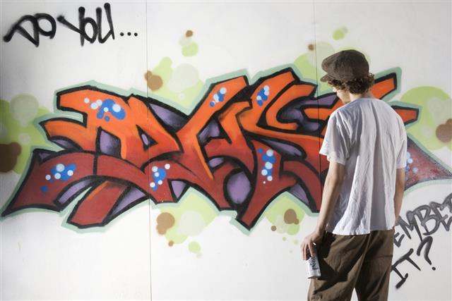 Teenager Graffiti Artist Spray Painting Wall Street Art, Rebelling, Vandalizing