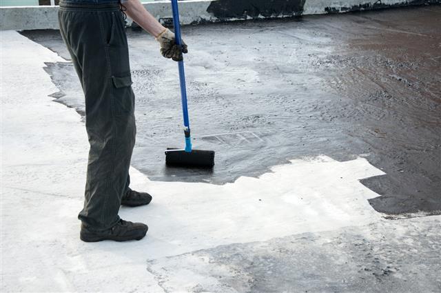 Roofer worker painting roller brush, waterproofing