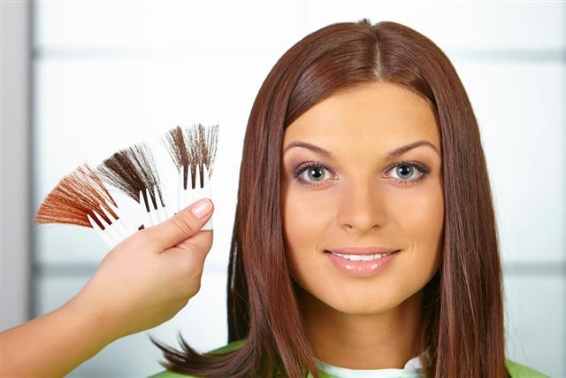 Hair salon. Woman choses color of dye
