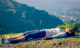 Woman relaxes in yoga asana Savasana outdoors