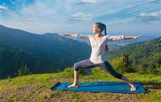 Woman doing yoga asana Virabhadrasana 2