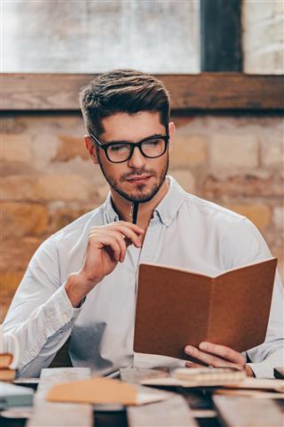 man looking at notebook