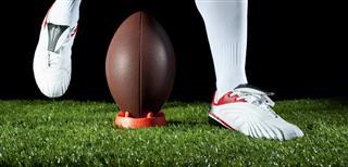 Boy Kicking a Gridiron Football