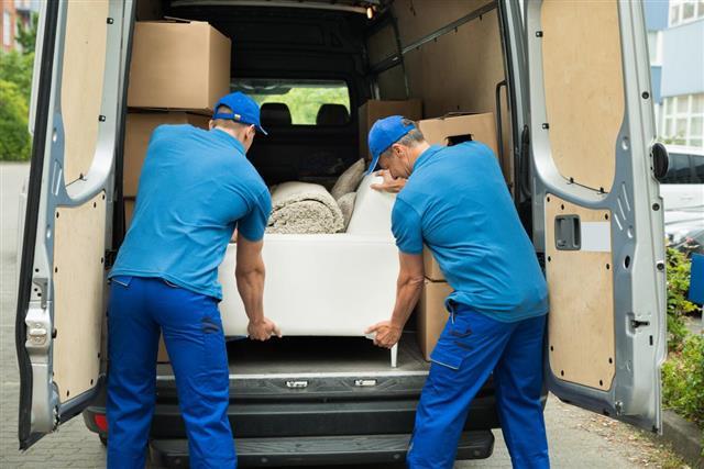 Workers Adjusting Sofa In Truck