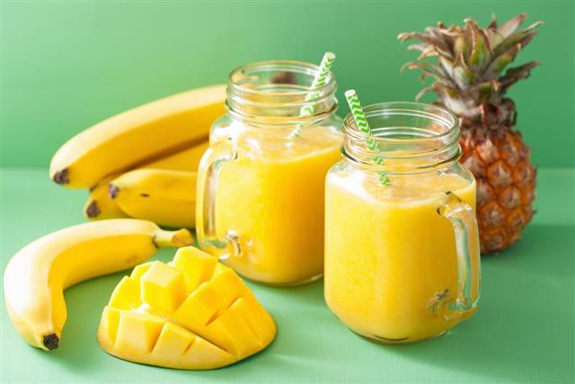 Healthy yellow smoothie with mango pineapple banana in mason jar