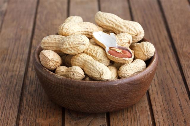 Rustic wood bowl of peanuts in shells