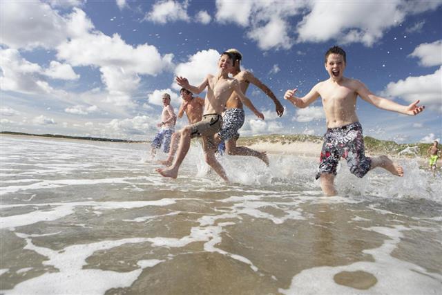 Teenage boys playing on beach