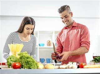 Portrait of newlyweds preparing dinner at home