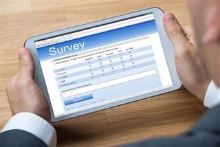 Businessman Giving Online Survey On Digital Tablet