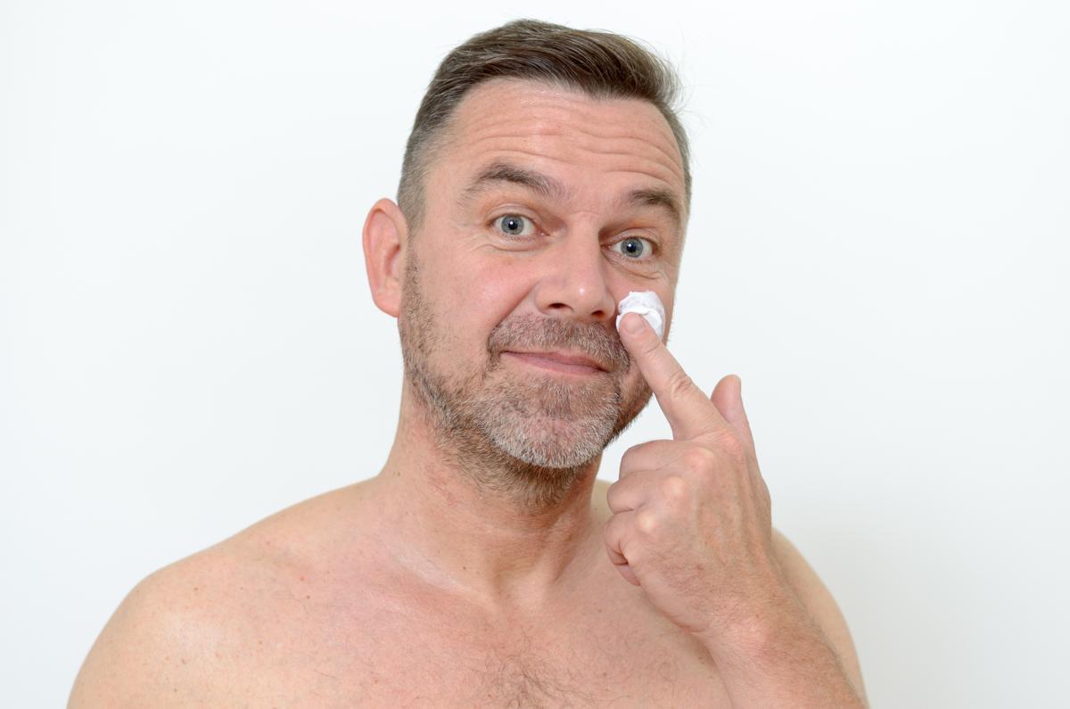 Mature man applying face cream closeup portrait high