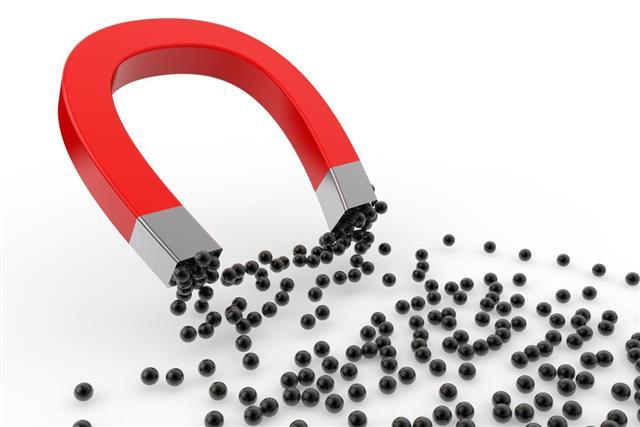 Magnet attracting black spheres