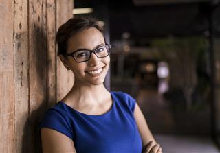 Portrait of confident businesswoman against wooden wall