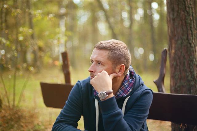 Man thinking moody portrait, sitting at autumn park