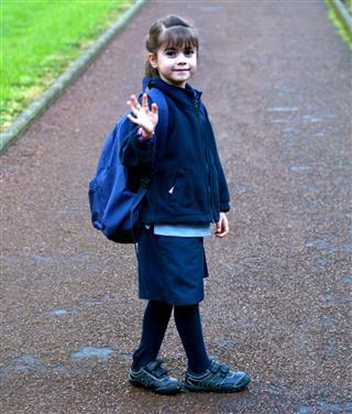 Little girl walks to school waves goodbye