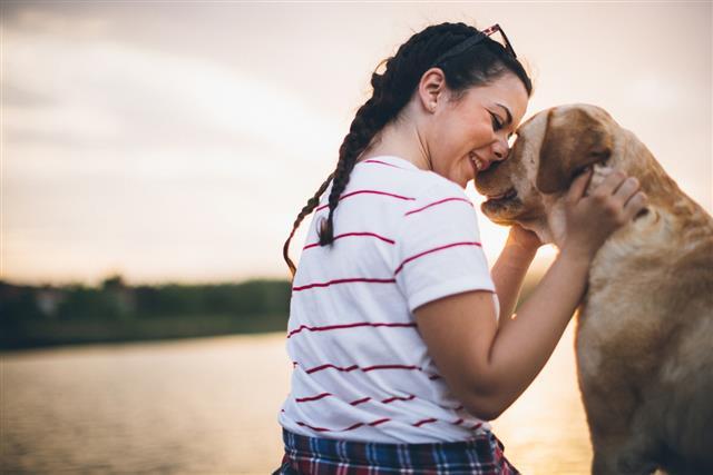 Teenager girl and her dog enjoying in golden sunset