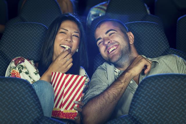 Couple eating popcorn in cinema