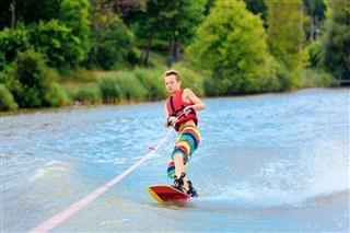 Active Boy Water Ski Boarding On Lake