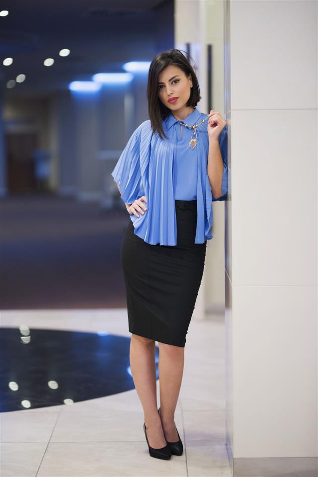 a woman wearing a black skirt on a light blue top