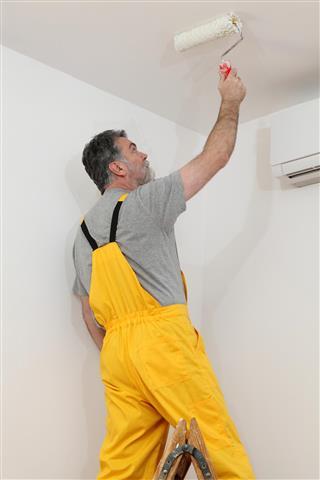 Worker painting ceiling in room