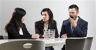 businessman yawning during meeting