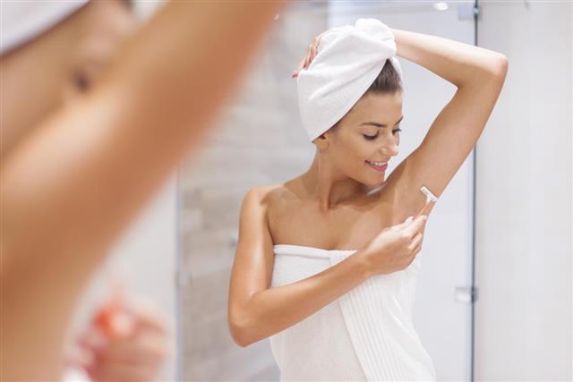 Woman shaving armpit
