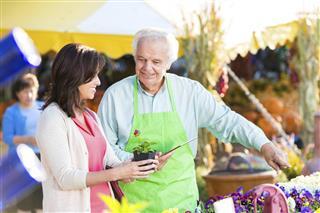 Senior shop owner helping customer in gardening store
