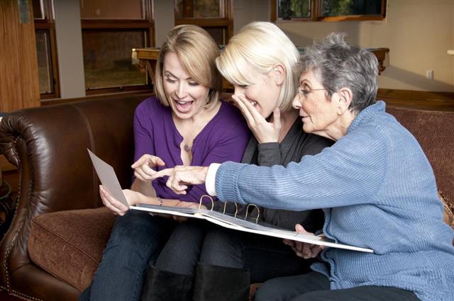 Three Generations of Women Look Through Photo Album
