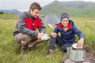 Couple cooking outside