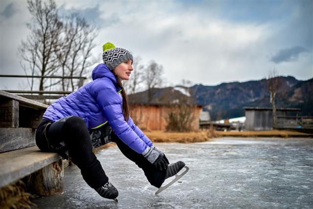 Woman Fixing Ice Skate Shoe