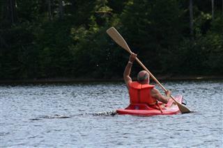 Senior Man Kayaking On Lake