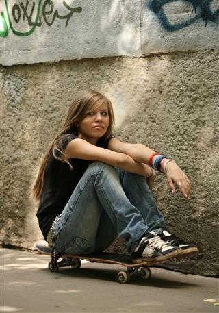 Girl Sitting On Skateboard