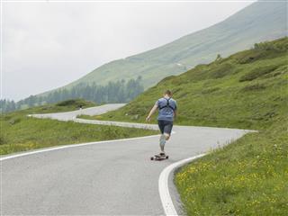 man longboards up mountain