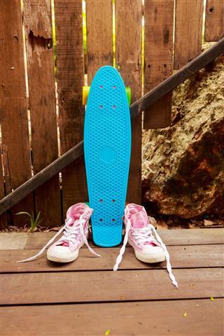 blue skate near wooden fence