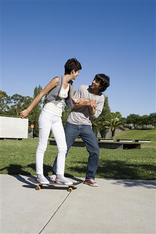 man helping girl to skateboard