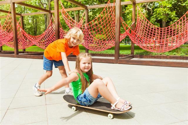 Boy pushes girl on skateboard