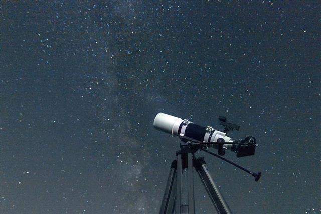 Telescope in real night sky. Refractor type. Telescope